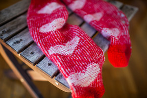 Red socks with heart pattern on wooden chair