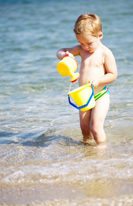 Adorable little boy playing in the sea