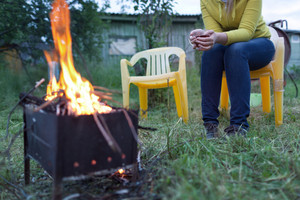 Woman with tea near the fire in yard
