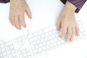 Hands of an old female typing on the keyboard and using mouse