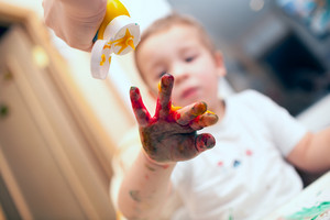 Pressing finger-paint on boys hand