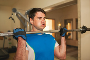 Strong young man exercising with barbell