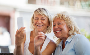 Modern mature women making happy mobile selfie