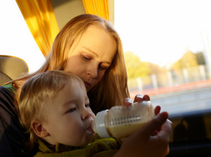 Mother is feeding her kid in the bus