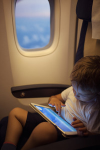 Boy spending time with tablet pc during flight