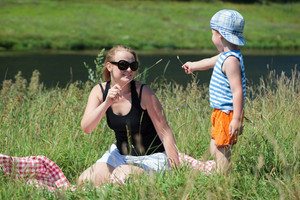 Mother and son playing with grass on the meadow