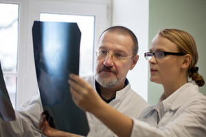 Senior and young doctors examining x-ray images