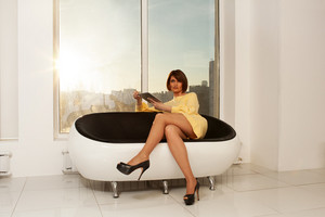 Elegant businesswoman sitting on sofa with crossed legs