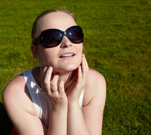 Young woman in sunglasses is sunbathing