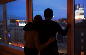 Couple embracing and looking at evening city together