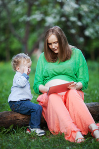 Pregnant mother with little son using touch pad in the park