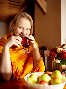 Young woman is drinking tea and smiling