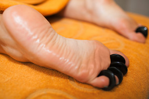 Woman getting hot stone massage on feet