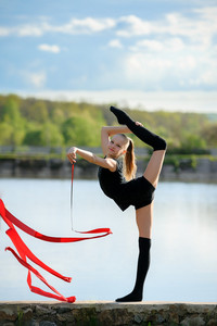 Rhythmic gymnast in vertical split with ribbon