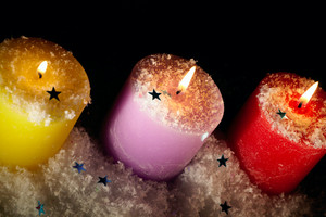 Three candles with artificial snow