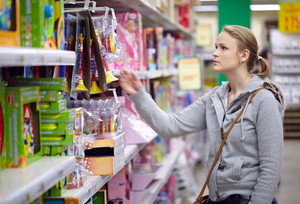Young woman is choosing toys for her kid