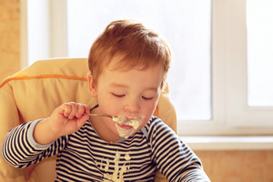 Two year old boy eats porridge in the morning