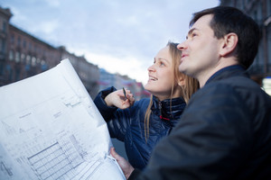 Couple holding blueprints admiring building