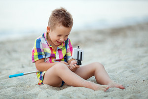 Happy boy with selfie stick and cell at the seaside