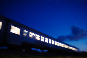 Illuminated train traveling past at night