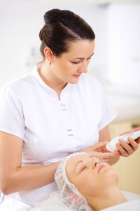 Cosmetician with cosmetic before procedure