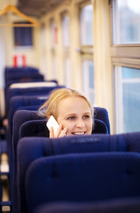 Smiling woman talking on the phone in train.