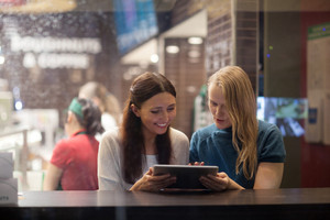 Two women talk cheerfully in the restaurant using electronic tablet