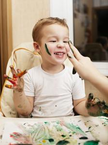 Happy little boy doing finger painting