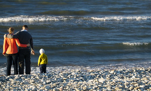 Family of three on pebble beach