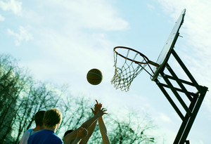 People playing basketball outdoors