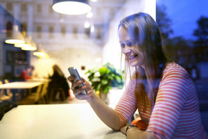 Young woman sitting in a restaurant using mobile