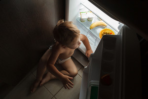 Little boy sitting near open fridge at night