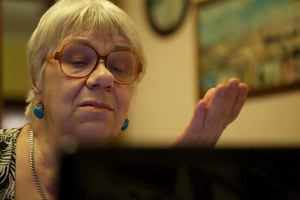 Senior woman gesturing as she reads on laptop