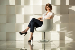 Elegant adult woman sitting in chair against of white modern wall