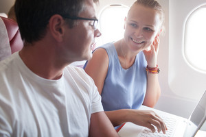 Happy young and woman with laptop in plane