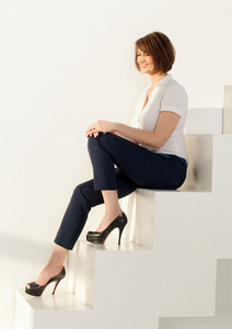 Smiling businesswoman sitting on steps with eyes closed