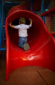 Boy is sitting at the slide hole