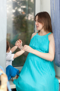 Pregnant woman plays with little boy