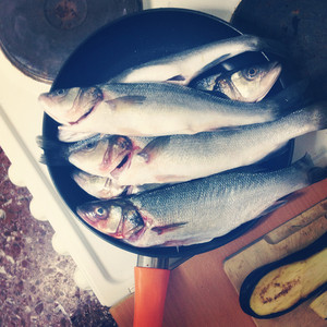 Fresh fish in a frying pan on the table