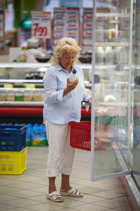 Woman taking milk from the fridge in supermarket
