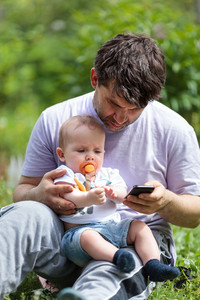 Father using a mobile with baby on his lap