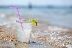 Glass of lemonade or water on beach by sea