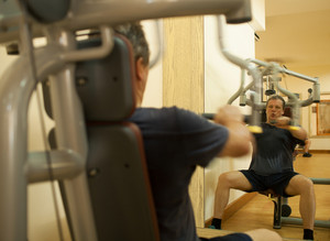 Mature man exercising on shoulder press machine
