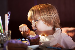 Little boy eating chocolate cake