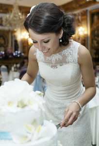 Smiling beautiful bride cutting the wedding cake