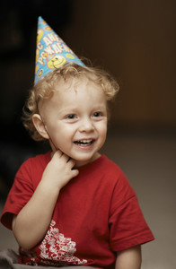 Cute happy young boy in a party hat