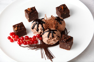 Chocolate ice cream with bonbons and red currants