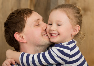 Happy father kissing little daughter