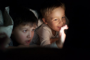 Two boys watching movie or cartoon on pad at night