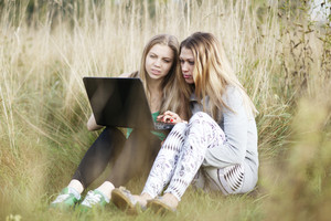 Female friends with laptop outdoor